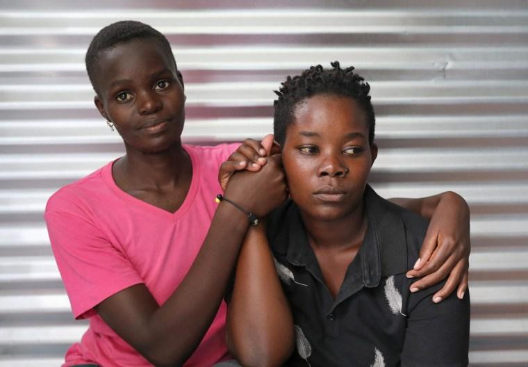 Image: Ugandan refugees Suzan Nakajiri and Eva Nabagala, both of the LGBT community, hold hands inside their shelter at the Kakuma refugee camp, in Turkana county