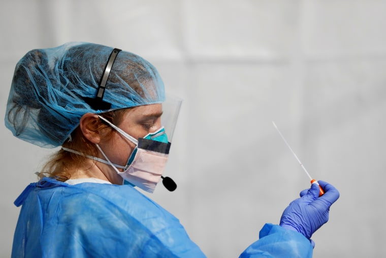 Image: Lindsey Leinbach looks at a coronavirus test swab at a facility in the Bronx, N.Y., on April 21, 2020.