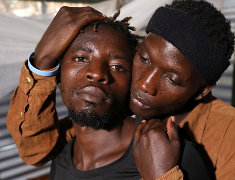 Ugandan refugees Kimuli Brian and Dennis Wasswa, members of the LGBT community, embrace each other inside their shelter at the Kakuma refugee camp, in Turkana county