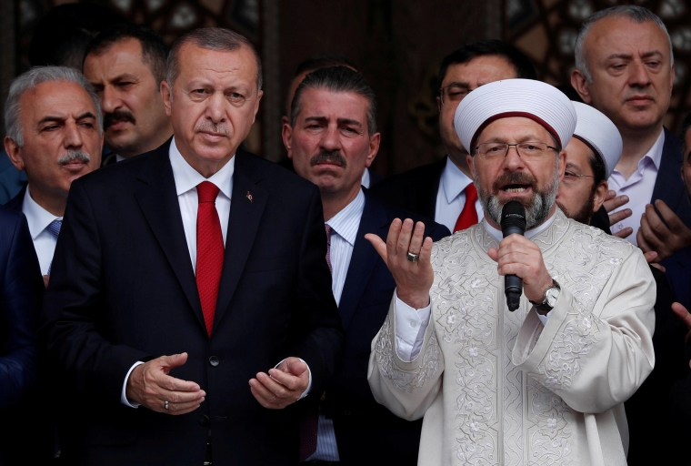 Image: Turkish President Tayyip Erdogan, accompanied by head of Turkey's Religious Affairs Directorate Ali Erbas, prays during the opening ceremony of a mosque in Istanbul, Turkey