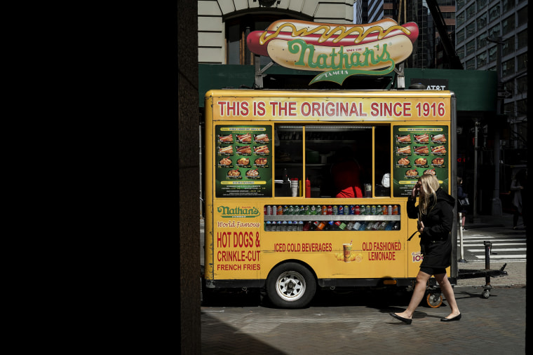 Image: A woman walks past a Nathan's hot dog cart on Wall Street in New York on April 12, 2019.