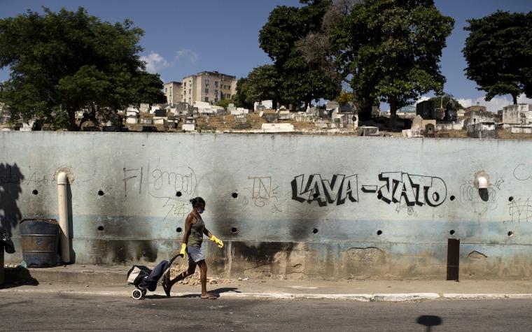 Image: A woman wearing a mask walks past Nossa Senhora das Gracas cemetery  in Rio de Janeiro, Brazil, on April 27, 2020.