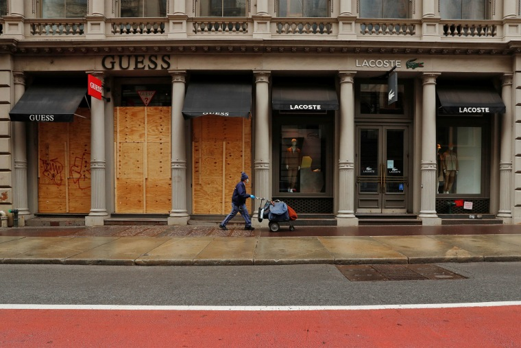 A postal worker walks past shuttered stores in New York City on April 27, 2020.