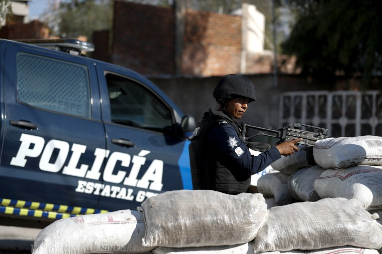 Police stand guard behind a parapet of sandbags, at the entrance to Santa Rosa de Lima, birthplace of a local cartel that goes by the same name, in Guanajuato state, Mexico on Feb. 12, 2020.