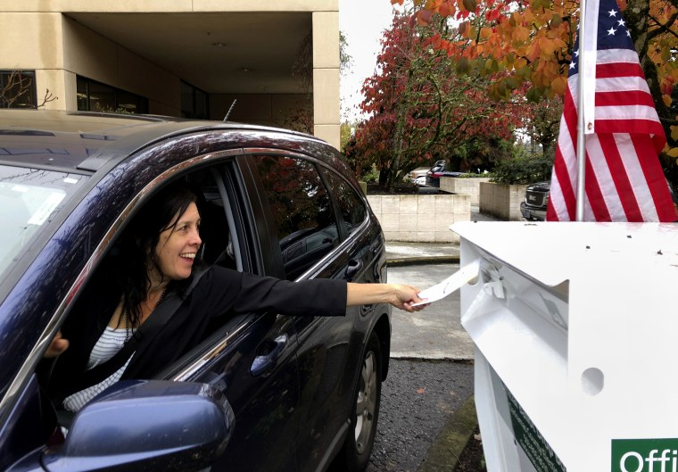 A voter in Lake Oswego, Ore., places her ballot in a designated drop box outside City Hall on Nov. 6, 2018.
