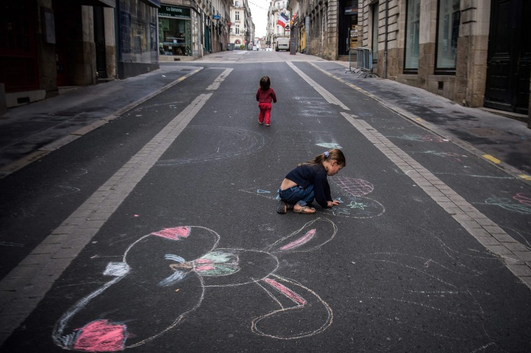 Image: A child draws with chalk on a road  in Nantes, on April 27, 2020, as the country is under lockdown to stop the spread of the COVID-19 pandemic caused by the novel coronavirus.