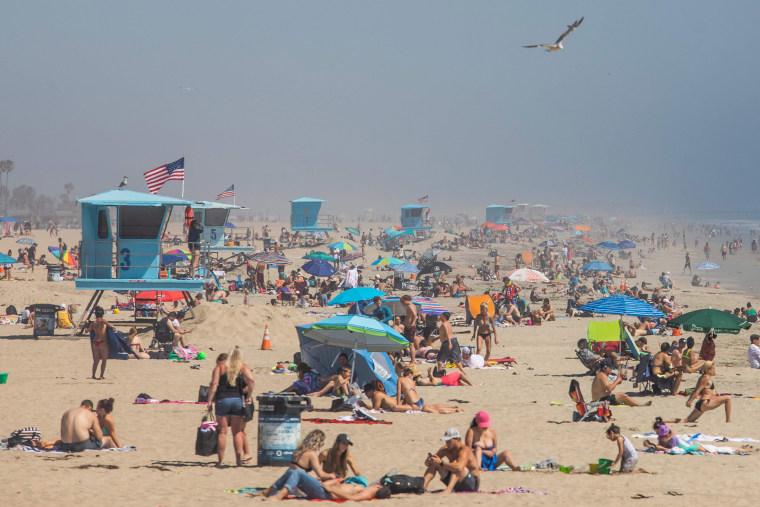 Image: People enjoy the beach amid the novel coronavirus pandemic in Huntington Beach, California on April 25, 2020.