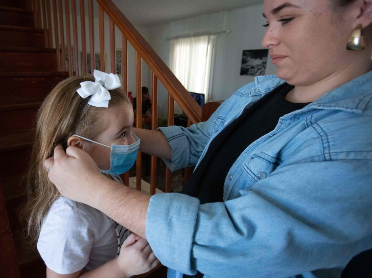 Image: Tabata helps her daughter Naidelin, 5, to put on her face mask prior to going out in Santa Cruz on the Canary Island of Tenerife,