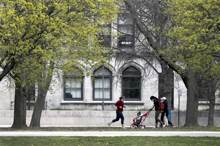 A runner, and two women wearing protective masks pass near the University of Chicago on April 27, 2020, in Chicago.