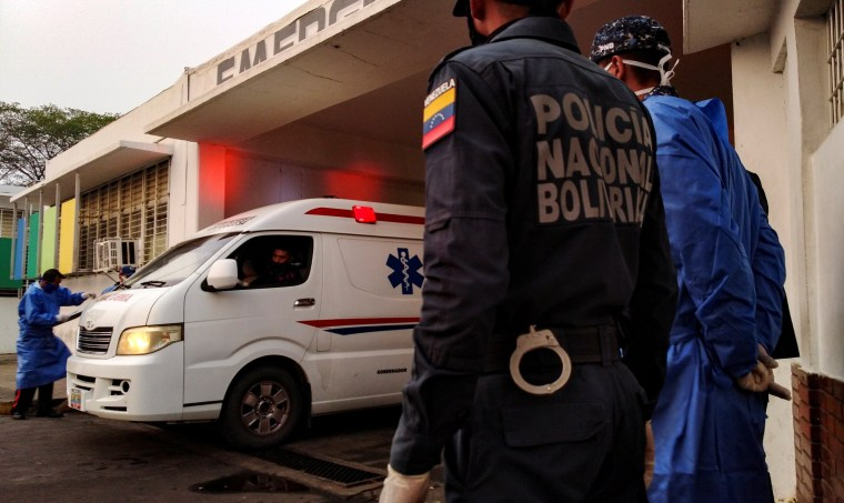 Image: Healthcare workers and members of the Bolivarian national police watch as an ambulance arrives with prisoners outside a hospital after a riot erupted inside a prison in Guanare