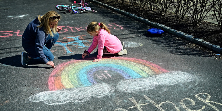 Mother and daughter draw inspirational chalk signs on sidewalk during pandemic