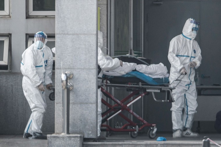 Image: Medical staff members carry a patient into the Jinyintan hospital, where patients infected by a mysterious SARS-like virus are being treated, in Wuhan in China's central Hubei province