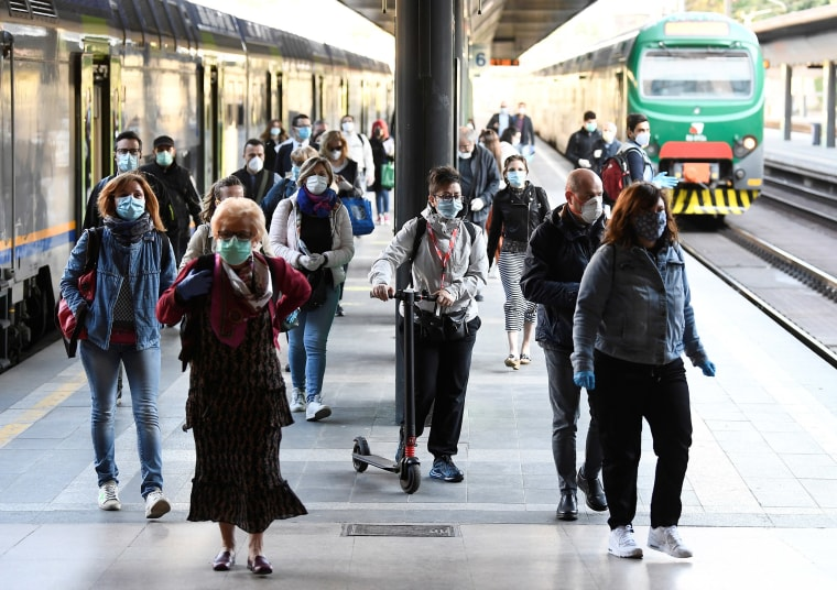 Image: People wearing face masks arrive at the Cadorna railway station, as Italy begins a staged end to a nationwide lockdown due to the spread of the coronavirus disease (COVID-19), in Milan,