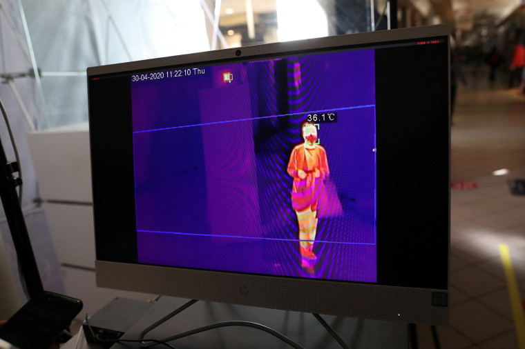 Image: A screen shows a thermal imaging system taking the corporal temperature of a customer carrying bags at the entrance to a reopened commercial center, following the coronavirus disease (COVID-19) outbreak, in Santiago, Chile