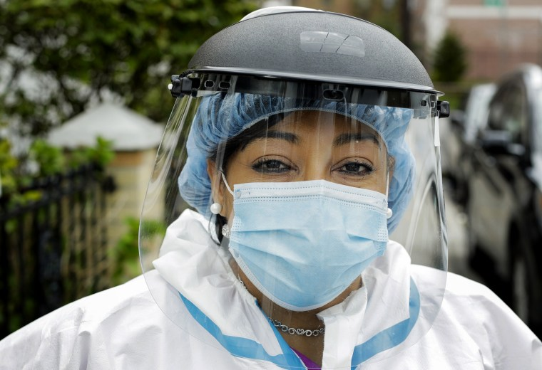 Image: Linda Silva, a nurse's assistant who tested positive for COVID-19, returns to work after recovering in Queens, N.Y., on April 30, 2020.
