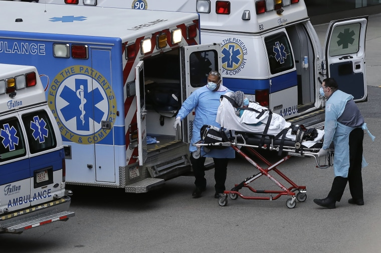 Image: Medical personnel remove a patient from an ambulance near an entrance to Massachusetts General Hospital