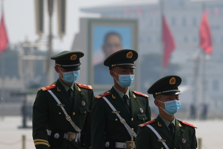 Paramilitary police officers wear masks as they patrol in Tiananmen Square in Beijing on May 1, 2020.Greg Baker / AFP - Getty Images