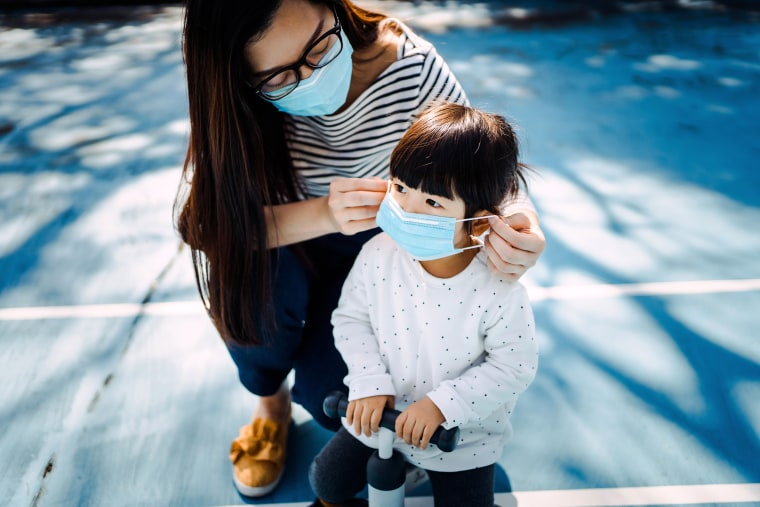 Image: Young mother putting on surgical mask for little daughter in the playground to prevent the spread of cold and flu and viruses