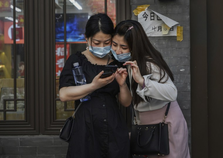 Image: Chinese women wear protective masks as they look at a mobile phone while standing in the street of a commercial district