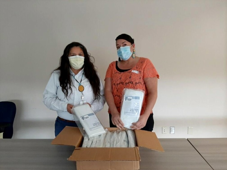 Image: Esther Lucero, left, CEO of the Seattle Indian Health Board, and Abigail Echo-Hawk, the board's chief research officer, with a box of body bags.