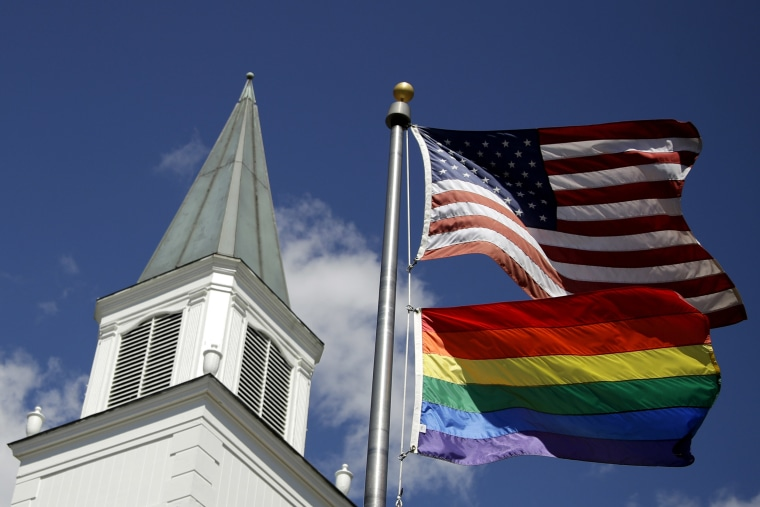 Image: A gay pride rainbow flag flies along with the U.S. flag in front of the Asbury United Methodist Church in Prairie Village, Kan.