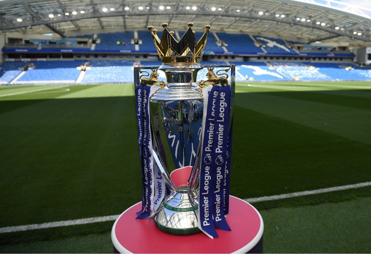 Image: The Premier league trophy sits beside the pitch ahead of the English Premier League football match between Brighton and Hove Albion and Manchester City