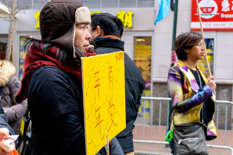 Manni Lee, one of the leaders of Grace Alive Fellowship, holds a sign during the Lunar New Year march in New York on Feb. 9, 2020.