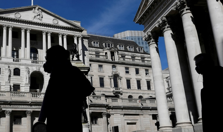 Image: People wearing masks walk past the Bank of England, as the spread of the coronavirus disease (COVID-19) continues, in London, Britain.