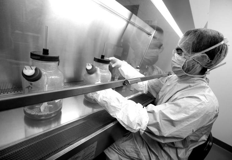 Image: A manufacturing associate works in a cell culture room where scientists are working on developing a vaccine