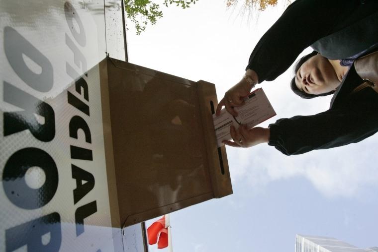 A voter drops off her election ballot at a drop box in Portland, Oregon