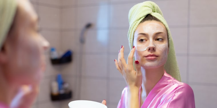 Woman putting facial mask in the bathroom