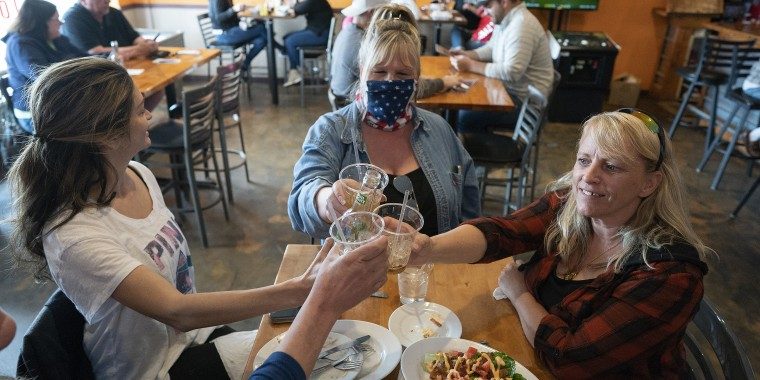 "Friends, Tracey, Cindy Coleman and Lori Stayberg meet for food and drinks at Jonesy's Local Bar on the first day of the bar reopening in Hudson, Wis., May 14, 2020. Wisconsin Gov. Tony Evers warned Thursday of ""massive confusion"" after the state Supreme Court tossed out the Democrat's stay-at-home order."