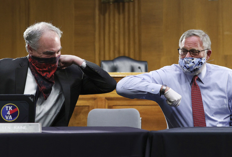 Sen. Tim Kaine, D-Va., left, and Sen. Richard Burr, R-N.C., greet each other with an elbow bump before the Senate Committee for Health, Education, Labor, and Pensions hearing, Tuesday, May 12, 2020 on Capitol Hill in Washington. Dr. Anthony Fauci, director of the National Institute of Allergy and Infectious Diseases, is to testify before the committee.