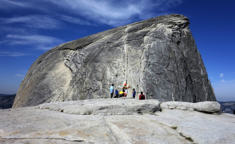 Hikers gather in the foreground as climbers use the assistance of cables to scale Half Dome in Yosemite National Park in California's Sierra Nevada on July 15, 2014.