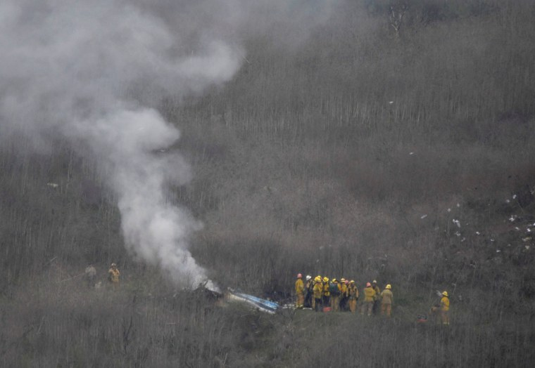 Image: LA county firefighters on the scene of a helicopter crash that reportedly killed Kobe Bryant in Calabasas