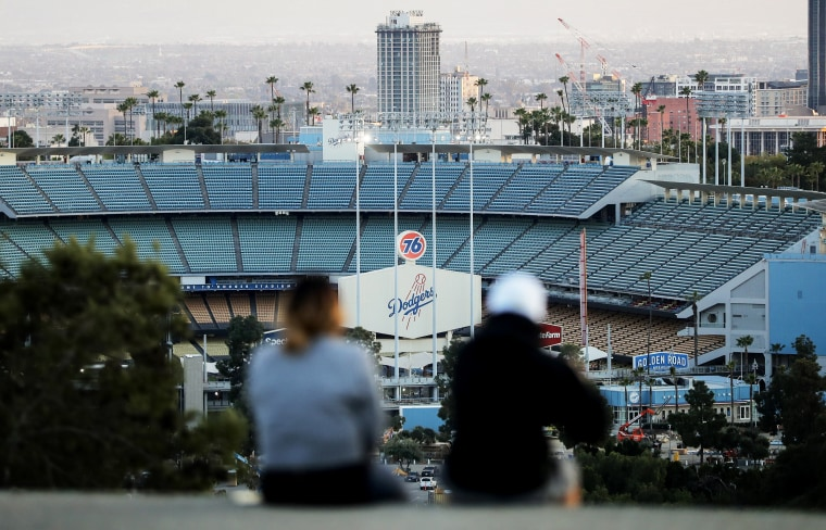 Image: People sit on a hill overlooking the empty Dodgers Stadium in Los Angeles on March 26, 2020.