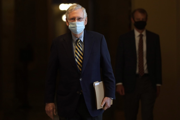 Image: Senate Majority Leader Sen. Mitch McConnell (R-KY) wears a mask as he walks through a hallway at the U.S. Capitol