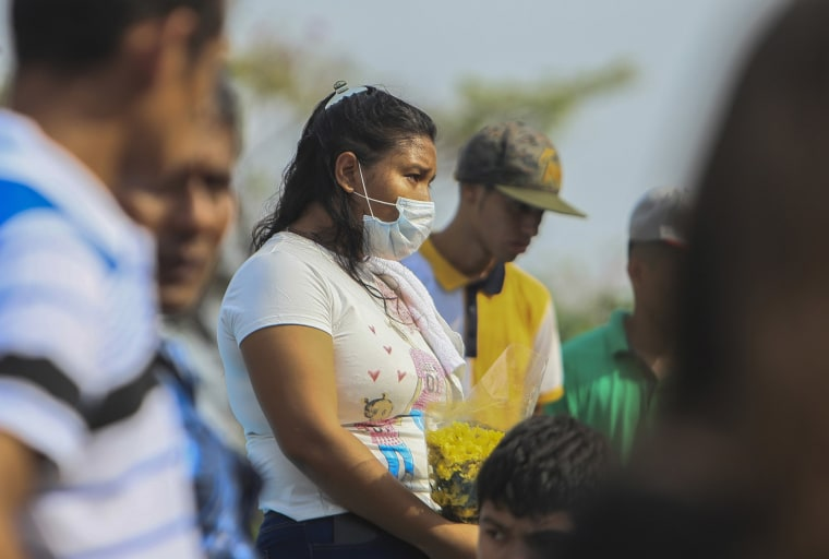 Image: A woman wears a mask against the spread of COVID-19 disease, as she attends a funeral at the Central cemetery of Managua, Nicaragua