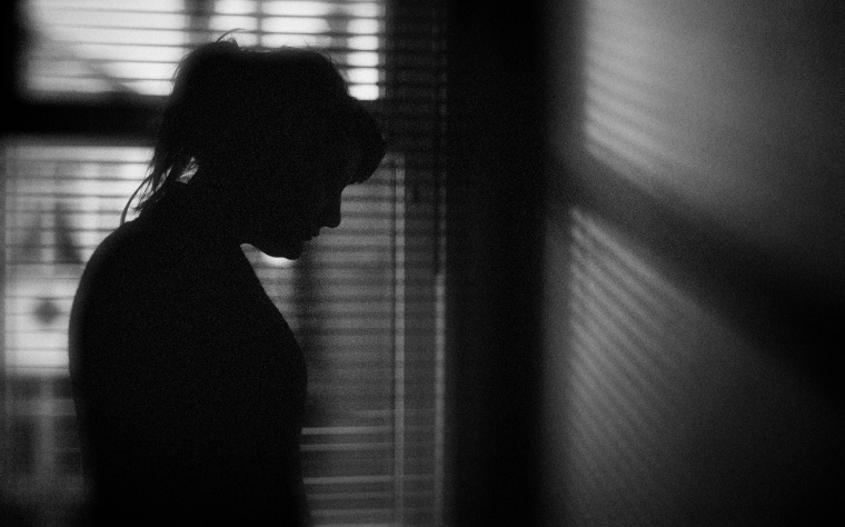 Image: The silhouette of a woman standing by a window.