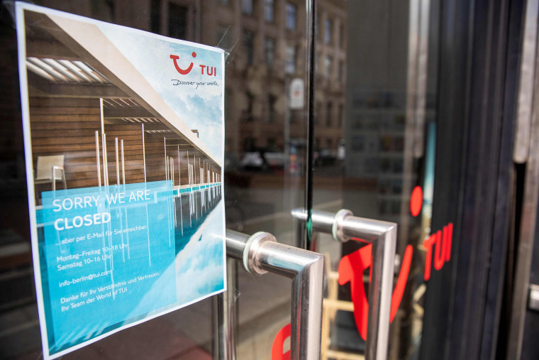 Image: A notice telling customers that they are closed on the door of a branch of the travel firm TUI in Berlin