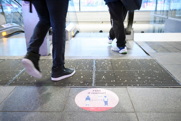 Image: A sticker on a street to ask people to keep social distances amid the new coronavirus pandemic in central Stockholm
