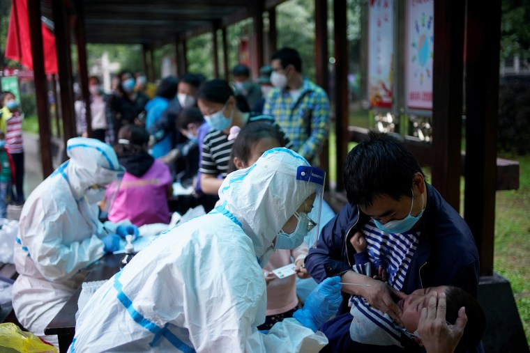 Image: A medical worker in a protective suit conducts a nucleic acid testing for a child at a residential compound in Wuhan, the Chinese city hit hardest by the coronavirus disease (COVID-19) outbreak, Hubei province