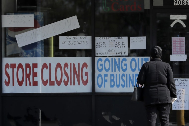 Image: A woman looks at signs at a store closed due to COVID-19 in Niles, Ill.