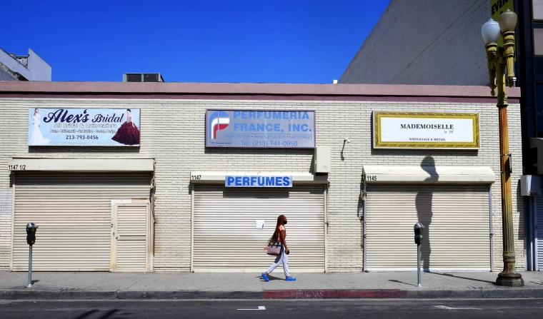 Image: A woman walks past closed storefronts in Los Angeles on May 4, 2020.