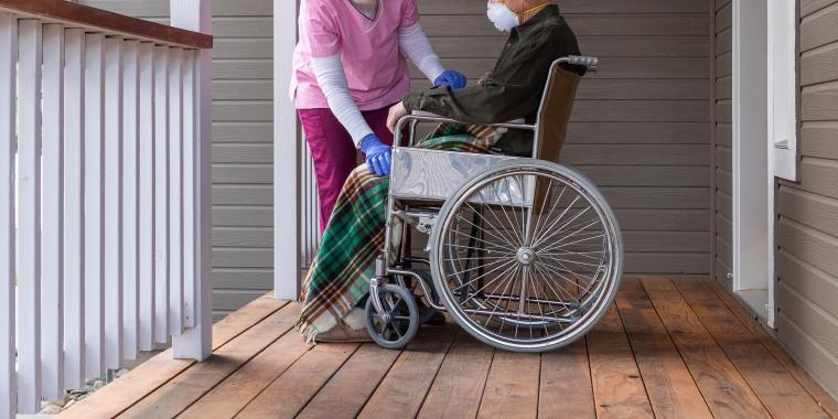 Image: Caretaker, nurse, man in wheelchair on porch, stock