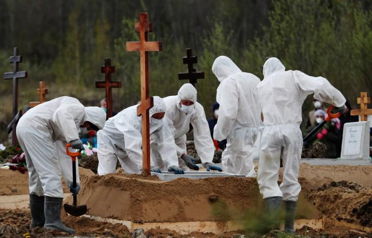 Image: Grave diggers bury a coronavirus disease victim in Saint Petersburg