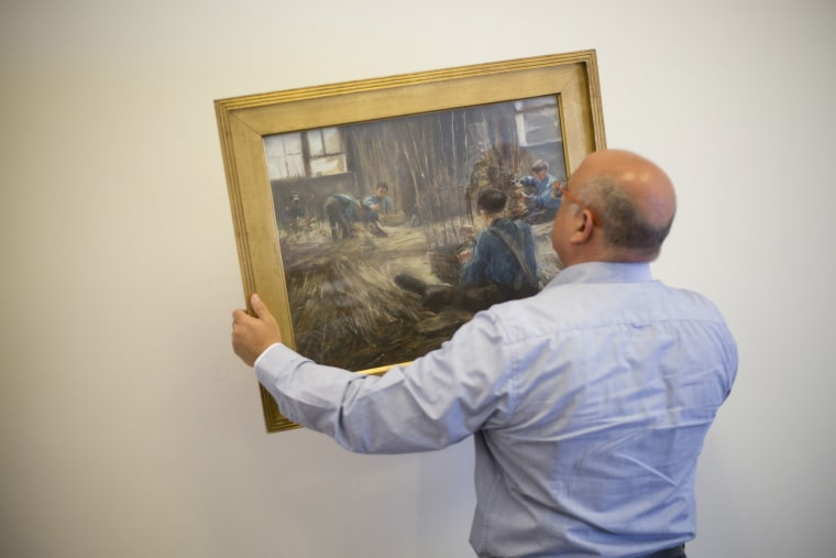 "Image: Meir Heller, the Jerusalem lawyer holds Max Liebermann's ""Basket Weavers\"" painting in a law office in Jerusalem,"