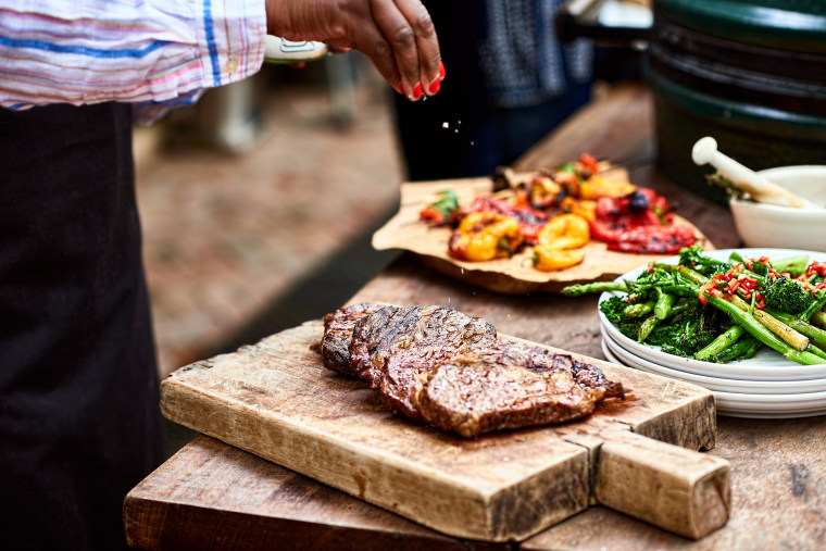Image: Woman sprinkling salt on freshly cooked steak
