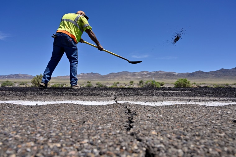 Image: A crack across the roadway is seen as Nevada Department of Transportation worker Jarrid Summerfelt repairs damage to U.S. Highway 95 after a strong earthquake struck near Tonopah