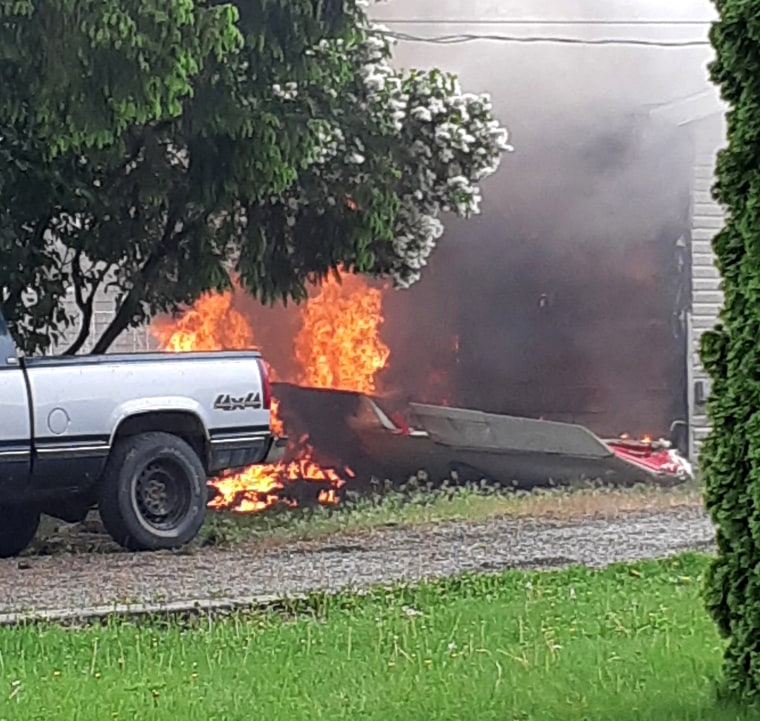 Image: Flames and debris at the site of the plane crash.